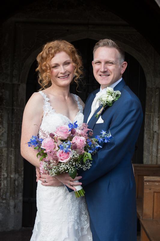Happy shot of couple outside St Michel's church in Warfield