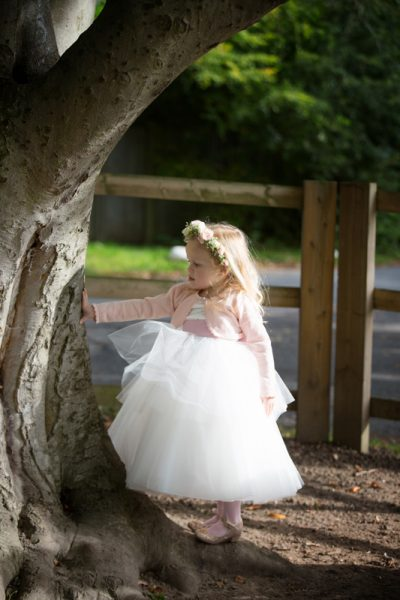 Flower girl playing in the garden at wedding at The Cricketers in Warfield