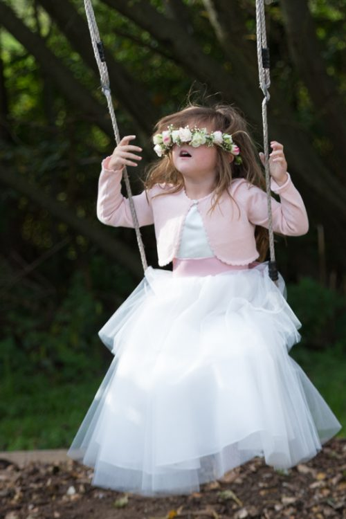 Amusing shot of cute flower girl at The Cricketers in Warfield, Berkshire