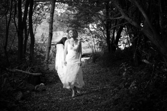 Bride and Groom walking in woodland near The Cricketers in Warfield, Berkshire
