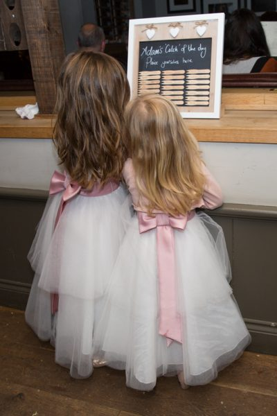 Flower girls intrigued by table plan at wedding at The Cricketers in Warfield