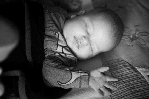 Sleeping baby with light shining on his face