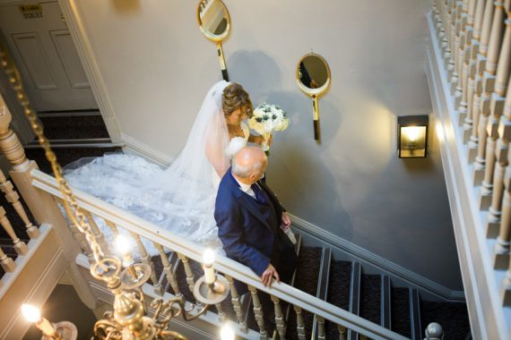 Bride walking down stairs towards her wedding at Old Bell Hotel in Hurley