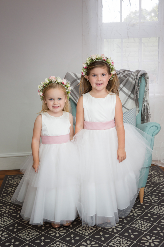 Flower girls posing for a photo before the bride leaves for the church