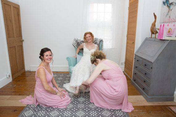 Bridal needs help putting on her shoes before her wedding