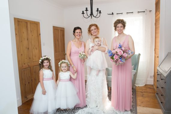 Bride, bridesmaids and cute flower girls before the wedding