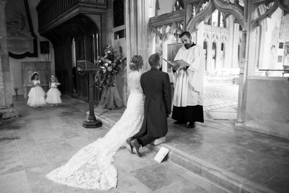 Bride and Groom at the alter with children looking on