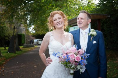 Bride and Groom looking happy outside St Michaels Church in Garfield
