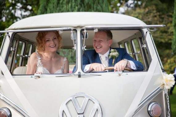 Bride and Groom laughing in vintage caravan at The Cricketers in Warfield