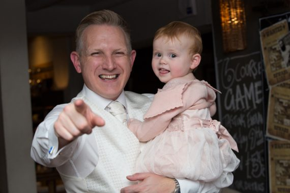Groom laughing with his young daughter