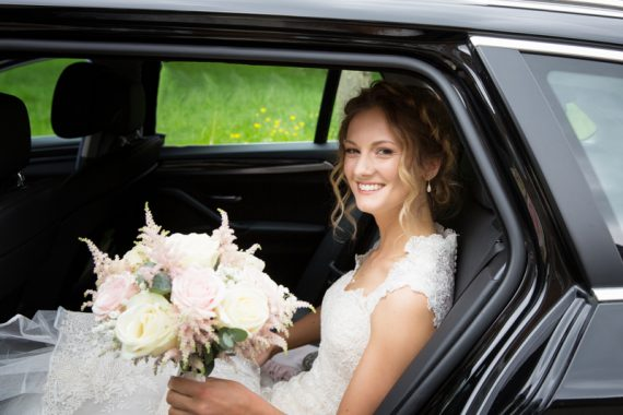 Beautiful bride in her bridal car arriving for her wedding at Blewbury Church in Oxfordshire
