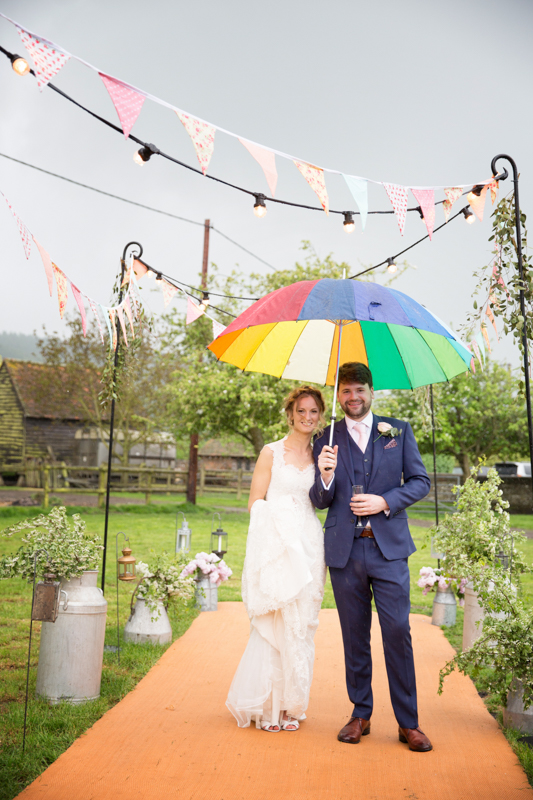 Bride and Groom with colourful umbrella at their teepee wedding near Henley on Thames
