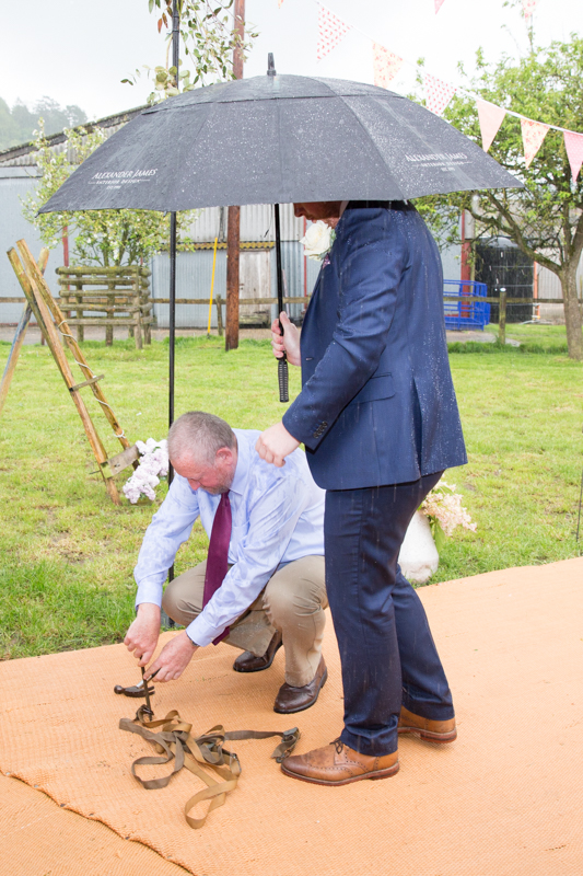 Bride's father repairing the wedding teepee in the rain near Henley on Thames