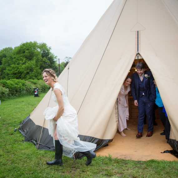 Bride running in her wellies in the rain at teepee wedding near Henley on Thames