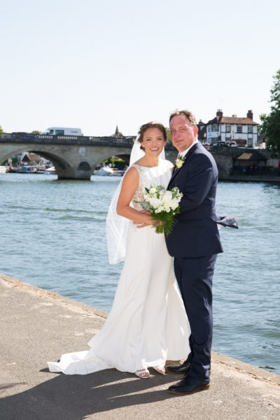 Bride and Groom with Henley bridge in the background during their wedding photographs