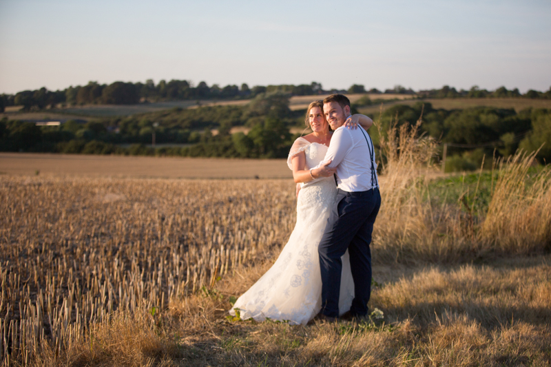 Bride and Groom looking happy in evening light at Notley Tythe Barn Wedding in Oxfordshire