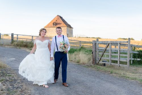 Bride and Groom walking past the dovecot at Notley Tythe Barn in Oxfordshire