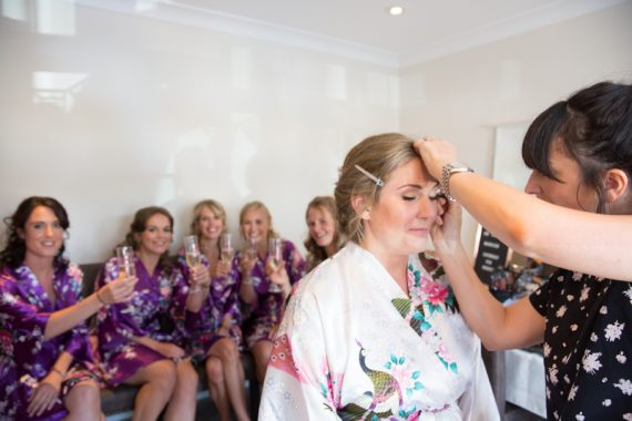 Bridal make up with bridesmaids in background