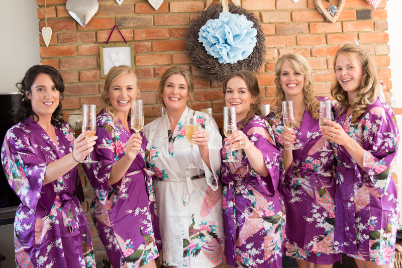 Bride and her bridesmaids drinking champagne