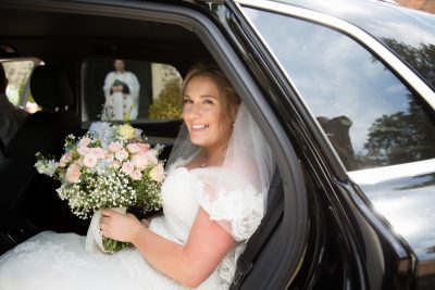 Bride in wedding car outside St Lawrence Church in West Wycombe