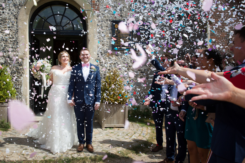 Bride and Groom and lots of confetti outside St Lawrence Church West Wycombe