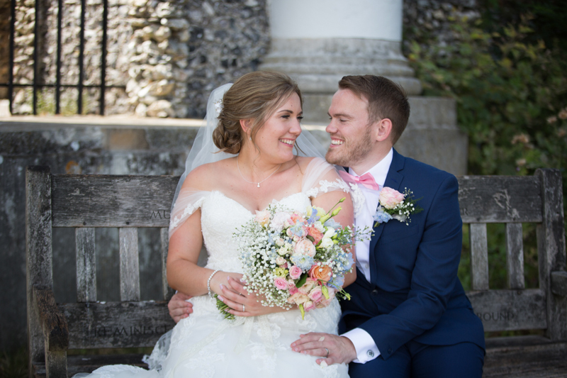 Bride and groom sitting outside Dashwood Mausoleum in West Wycombe