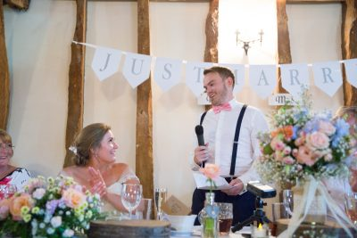 Groom looking at his wife during speeches at Notley Tythe Barn wedding