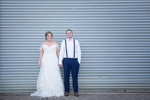 Bride and Groom against a farm door at Notley Tythe Barn