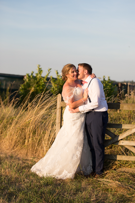 Couple leaning against a fence at their Notley Tythe Barn Wedding