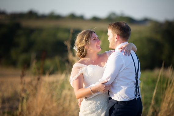 Bride and Groom in a field at their wedding at Notley Tythe Barn