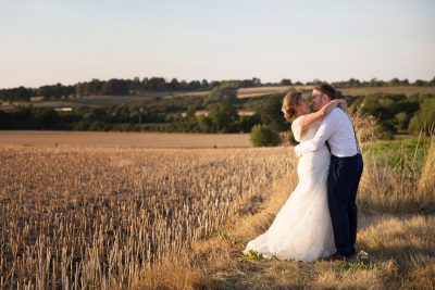 Couple in evening sun in field at Notley Tythe Barn Wedding
