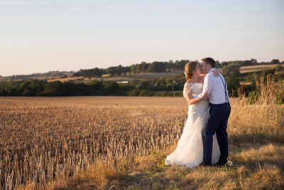 Couple kissing in field at sunset at Notley Tythe Barn
