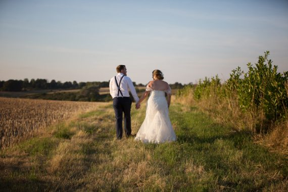 Couple walking in field at sunset at Notley Tythe Barn Wedding