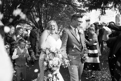 Couple looking happy during confetti at their wedding