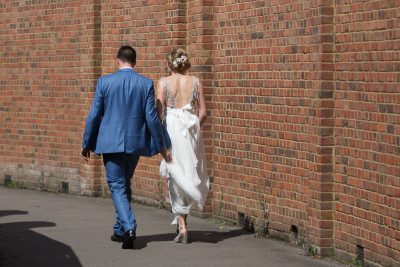 Back view of Bride and Groom walking towards the river in Henley