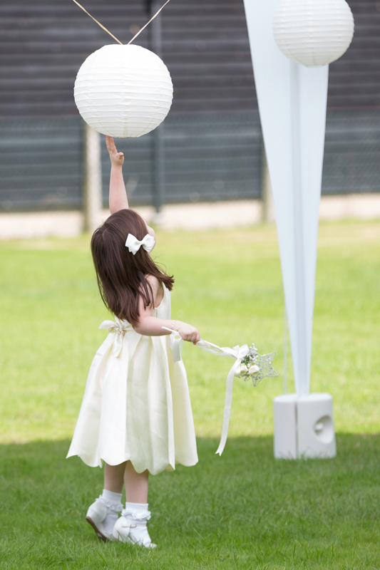 Flower girl reaching for lantern at Remenham Club in Henley