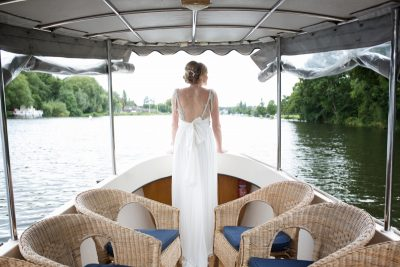 Back view of bride on boat on river thames in Henley