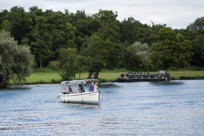 Bride and Groom arriving in a vintage launch boat at Remenham Club Wedding in Henley