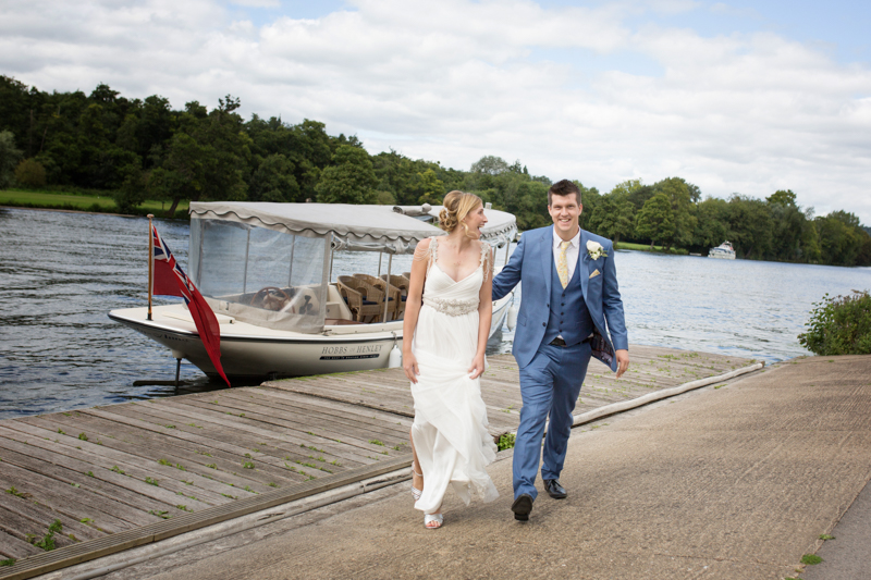 Bride and Groom looking happy by the river in Henley on Thames