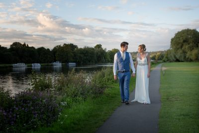 Bride and Groom enjoying evening walk by the river thames at their Remenham Club wedding