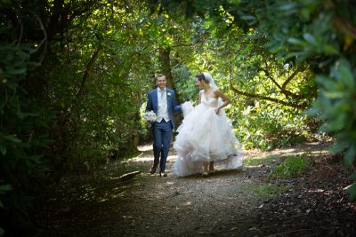 Bride and Groom walking in the woods at Tylney Hall