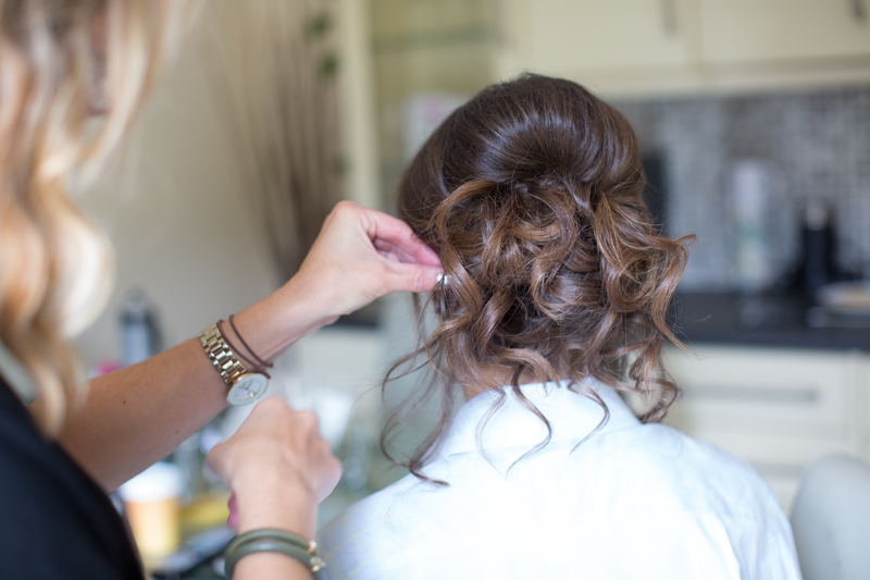Bride getting her hair done at her wedding