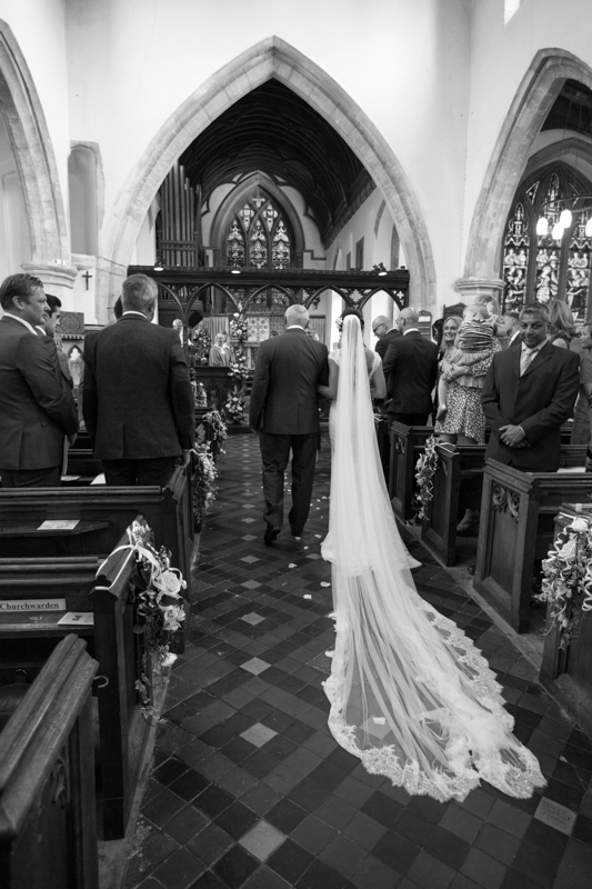 Bride walking down the aisle with a very long veil