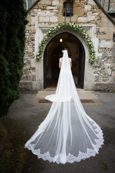 Bride with long veil outside church