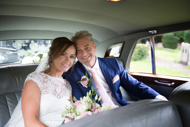 Bride and Groom in back of their wedding car in Marlow