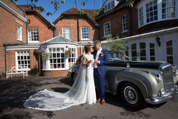 Bride and Groom posing in front of wedding car in Marlow