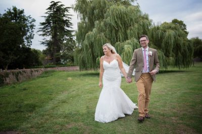 Bride and Groom walking hand in hand at their wedding in Thame
